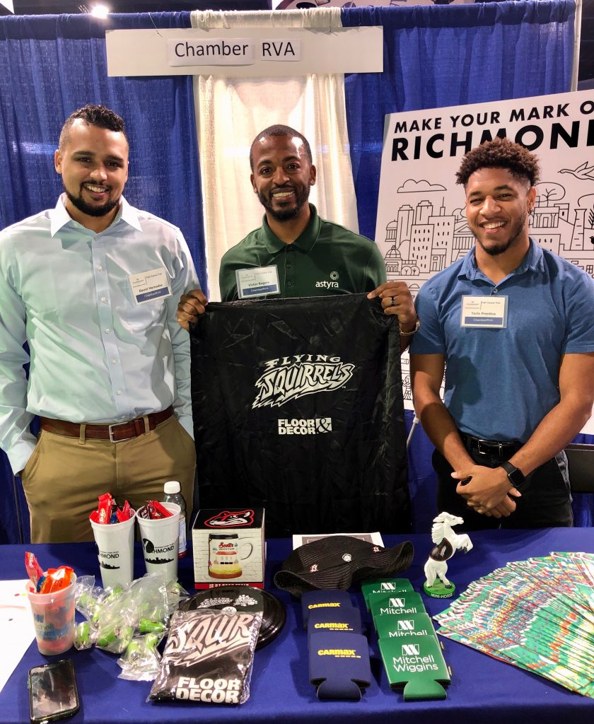 David, Victor and Torin all pose together smiling behind the ChamberRVA table. Victor is holding up a black bag with the Flying Squirrels logo in white.