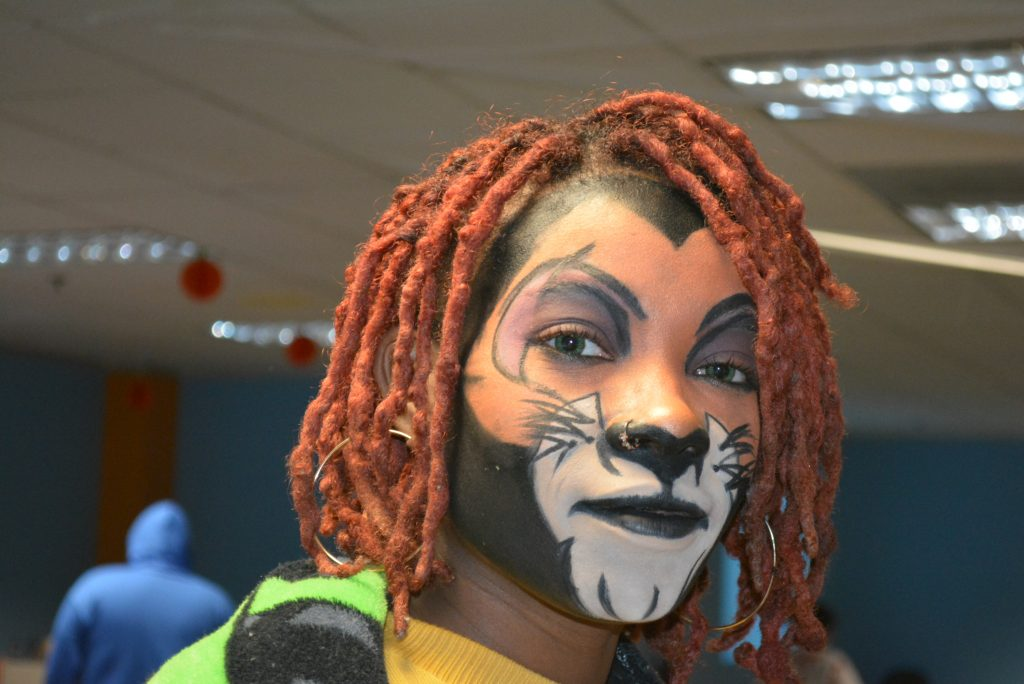 Kimani Jones looks at the camera with her face painted to look like Scar from The Lion King.